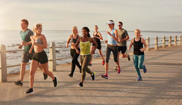 Runners running on street by the seaside