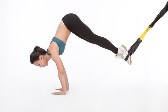 Core body excercise concept. Beautiful lady training with suspension trainer sling. Young attractive woman doing suspension training with fitness straps in studio.