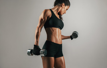 Strong woman lifting weights over gray background