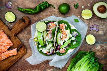 Preparing healthy lunch snacks. Fish tacos with grilled salmon, red onion, fresh salad leaves and avocado cilantro sauce on vintage stone background. Recipe for Cinco de Mayo party. Top view.