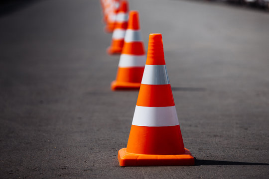 bright orange traffic cones standing in a row on dark asphalt