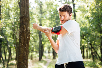 Athletic sportsman with handband standing and doing exercises in forest