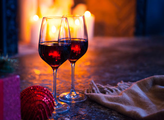 Two glass with red wine on Christmas tree and fireplace backgrou