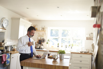 Man in a tie stands holding cup, using laptop in kitchen
