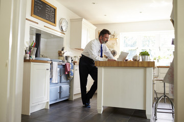 Man in tie in kitchen using laptop, full length, low angle