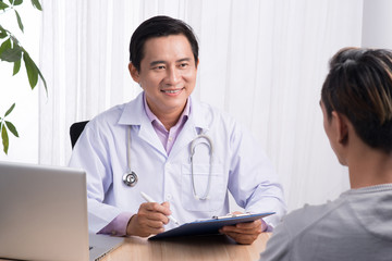 Confident asian male doctor discussing diagnosis with patient in