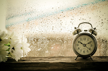Flower and retro alarm clock on table in front the rain