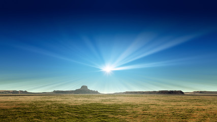 a desert scenery with sun rays in the blue sky