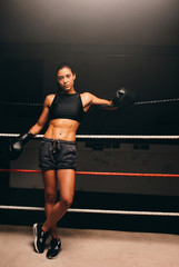 Young  female boxer leaning against ropes in boxing ring
