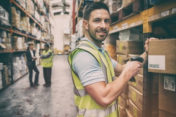 Warehouse worker scanning box while smiling at camera
