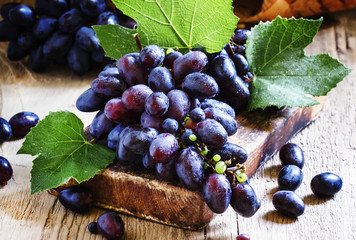 Blue grapes on old wooden table, selective focus