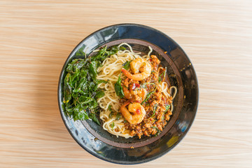 Instant noodles with Spicy fried shrimp and pork with chilli & Basil leaves in bowl on wooden background - Thai food