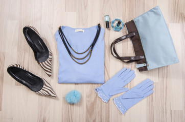 Winter sweater and accessories arranged on the floor. Woman blue and brown accessories, high heels, necklace and gloves lied down.