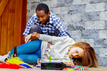 Woman wearing casual clothes lying drunk passed out on wooden surface, man sitting beside her trying to get contact by touching and grabbing womans arm