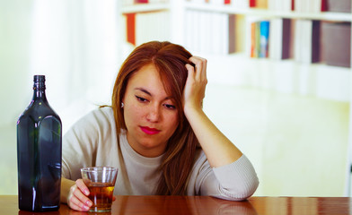 Attractive woman wearing white sweater sitting by bar counter lying over desk next to glass and bottle, drunk depressed facial expression, alcoholic concept