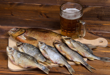 Dry fish on wooden background with beer
