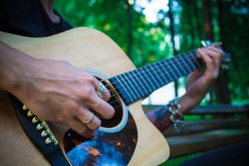 Man with tattoo playing classical guitar