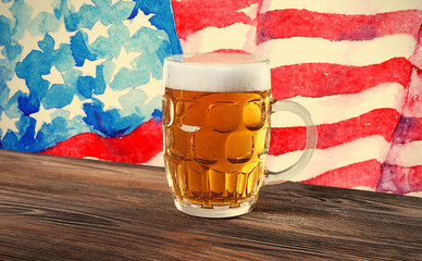 Glass of beer on wooden table. USA flag background.