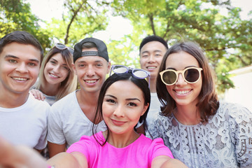 Group of happy teenagers taking selfie on street
