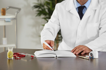 Male doctor with medical recipe book. Herbal medicine concept