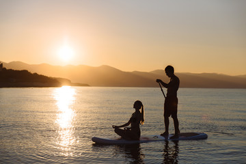 Silhouette of perfect couple engage standup paddle boarding