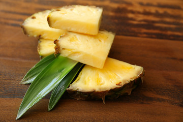 Pineapple slices on wooden background