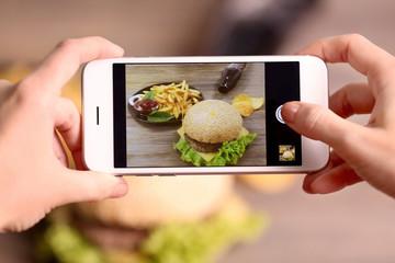 Woman taking photo of hamburgers on smart phone