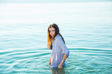 woman on sea get into the water in wet shirt