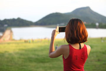 Young and pretty Woman taking dam photo with her smartphone
