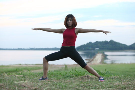 Yoga virabhadrasana II warrior pose by woman on lawn