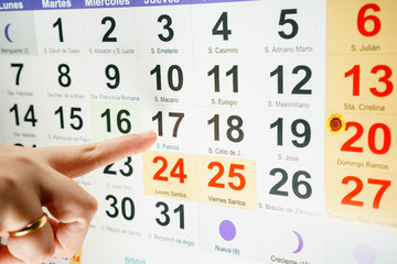 Finger pointing at day of week on calendar