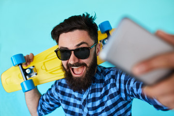 Young hipster with beard in glasses taking selfie and smiling isolated on the blank white background