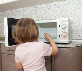child  trying to turn on  microwave