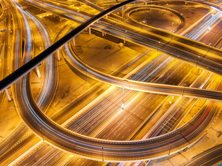 Extraordinary thoroughfare leading to Abu Dhabi during night rush hour near biggest skyscrapers. Traffic jam with multiple cars. Dubai, United Arab Emirates.