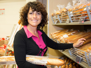 Woman choose Fresh baked bread at supermarket