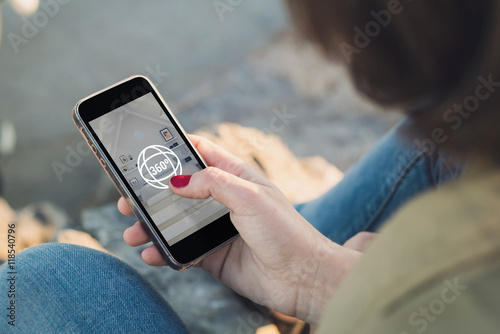Fotobehang Woman looking at her smartphone with 360 degree view