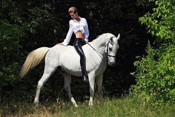 Beautiful model horseback riding in forest