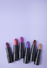 Aerial view of assorted lip stick make up on a pastel purple background forming a page footer