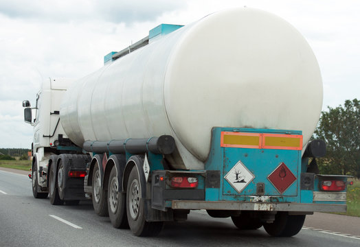White gas tanker truck on highway.
