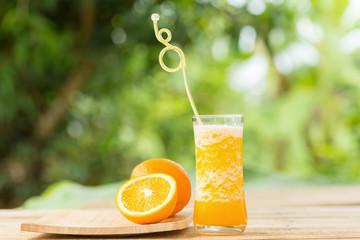 Glass of Orange Smoothie on garden background
