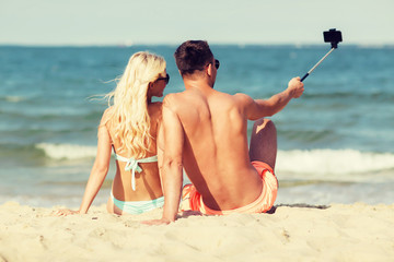 happy couple in swimwear sitting on summer beach