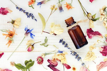 Aromatic essential oil. Top view dropper bottle among colourful dried flowers, medicinal herbs gathering, scattered white wooden table.   Fototapete