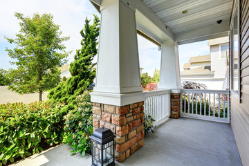 Concrete floor porch with wooden railings and brick trim