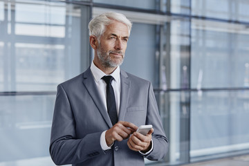 Confident businessman using cell phone