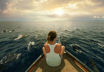 Young woman sitting on the boat and filmed a flock of dolphins