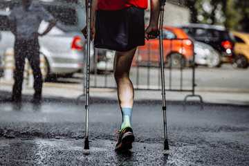 Wall Mural - male athlete with a disability without a leg on crutches running marathon