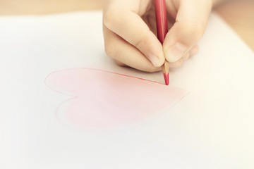 Child is drawing red heart