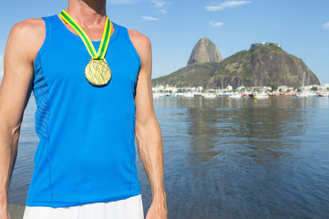 First place athlete wearing gold medal standing outdoors at Botafogo Bay in Rio de Janeiro, Brazil