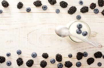 Yogurt with blueberries, teaspoon, blackberries and blueberries on the edges, a top view