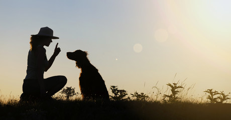 Silhouette of a female as training her dog - website banner